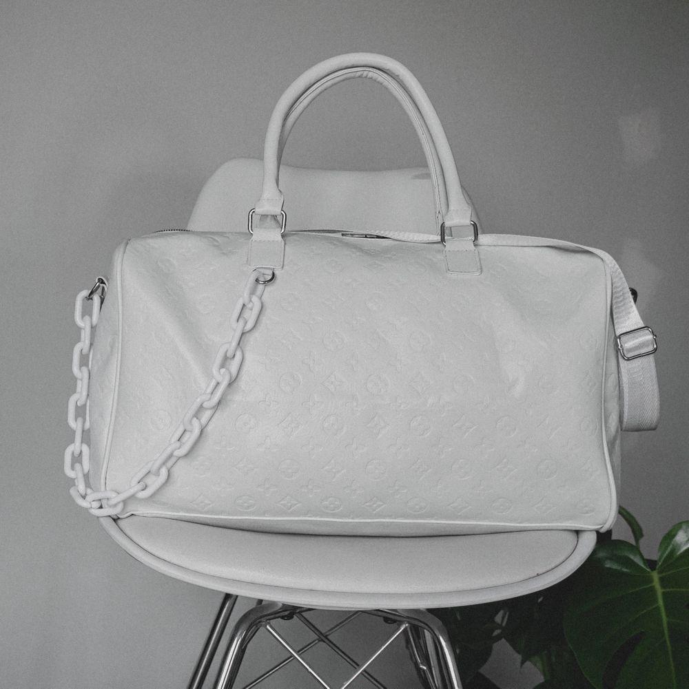 """Snygg, stilren väska inspirerad utav Louis Vuitton. Helvit med vit plastkedja. Rymmer förvånansvärt mycket, kan användas som """"weekend""""-bag. Använd 1 gång och har, tyvärr, legat i garderoben sedan dess.. Väskor."""