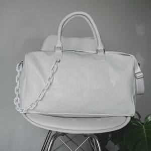 """Snygg, stilren väska inspirerad utav Louis Vuitton. Helvit med vit plastkedja. Rymmer förvånansvärt mycket, kan användas som """"weekend""""-bag. Använd 1 gång och har, tyvärr, legat i garderoben sedan dess."""
