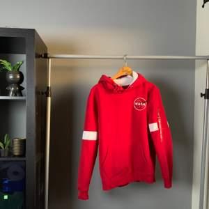 En röd hoodie ifrån Alpha Industries med vita detaljer. Använd få gånger då jag tröttnat på den. Om du vill ha bild hur den sitter på kan du gärna skriva till mig :) Nypris: 1000kr