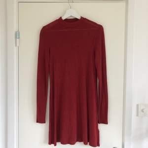 Fin röd klänning i ett mjukt och luftigt material. Passar fint till hösten då det också går att ha den instoppad eftersom det är ett såpass tunt tyg.