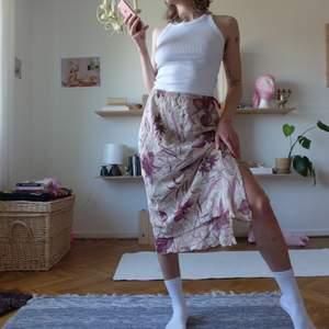 Perfekt sommarkjol! Beige med röd/lila blommor, volang och slits. Markerad storlek L men passar S/M/L. Viscose, polyamid.
