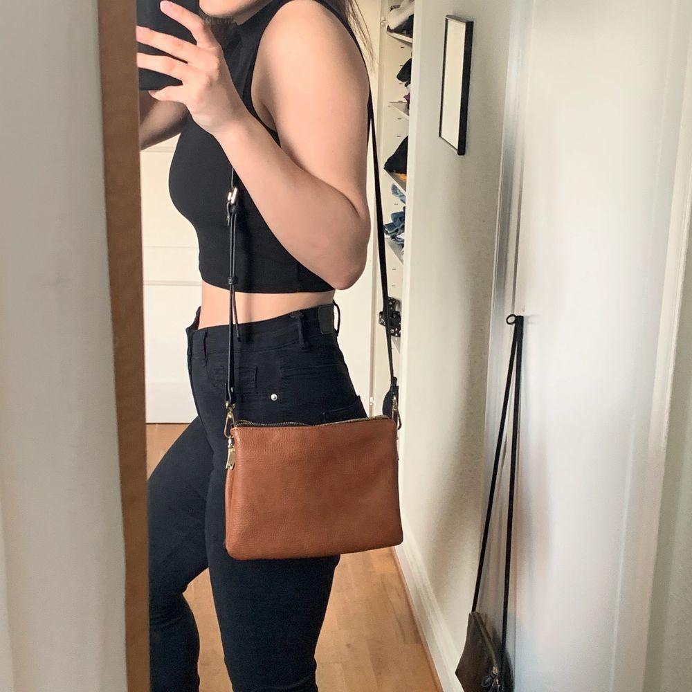 Inte riktigt läder. Väskan är köpt på Åhlens. Jättefin väska med flera fack, så den får plats med mycket. Justerbar axelband. Använd 2-3 gånger, så den är som ny! Frakt är inkluderad i priset.. Väskor.