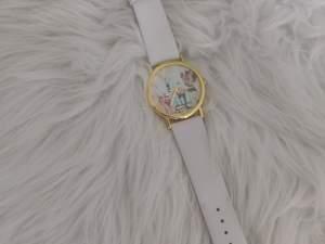 Vintage klocka med vitt fakeläder-band och urtavla med blommigt motiv samt guldiga detaljer. Köpare står för frakt. ✨