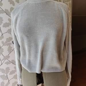 Grå stickad tröja med hål över axlarna från HM, storlek S, bra skick. 50kr +frakt