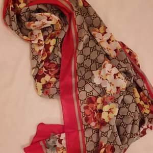 Så vacker sjal/scarf från Gucci! Materialet är i silke och passar både runt halsen, knyta runt ena axelbandet på väskan eller över axlarna. Fina tryck med blommor, röda detaljer och den klassiska logotypen🌸