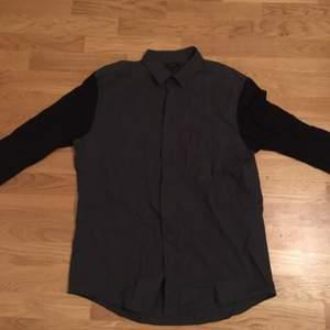 En grå skjorta med svarta ärmar från Cos, använd ett fåtal gånger.