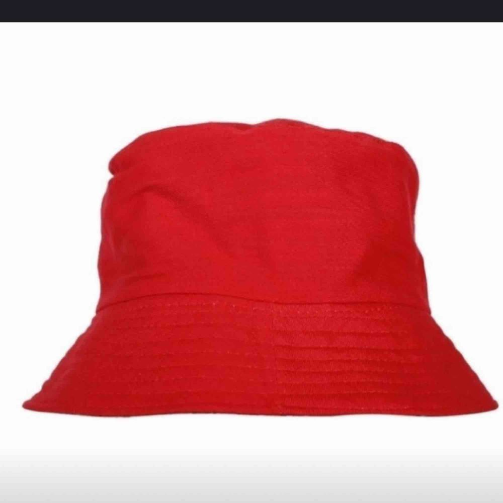 En röd bucket hat. Frakten ingår i priset ✨. Accessoarer.