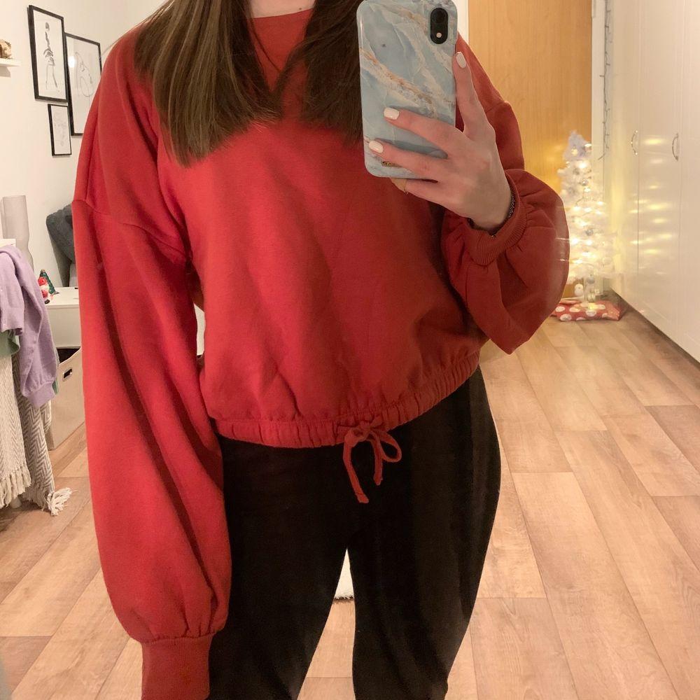 Röd sweatshirt med ballongarmar, det går att spänna i midjan med snöret, knappt använd, frakt tillkommer ❤️. Tröjor & Koftor.