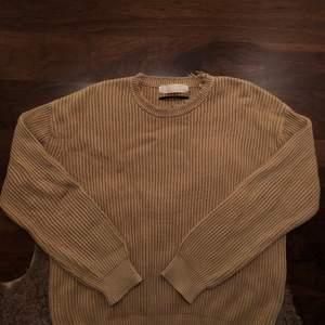 Stickad tröja från Adnym atelier. Distressing runt nacken. Guld/sand färgad
