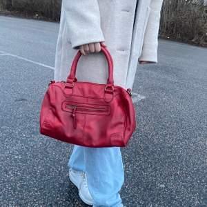 En röd handväska, passar till det mesta och man får plats med mycket. Säljer för använder tyvärr inte lika mycket längre.
