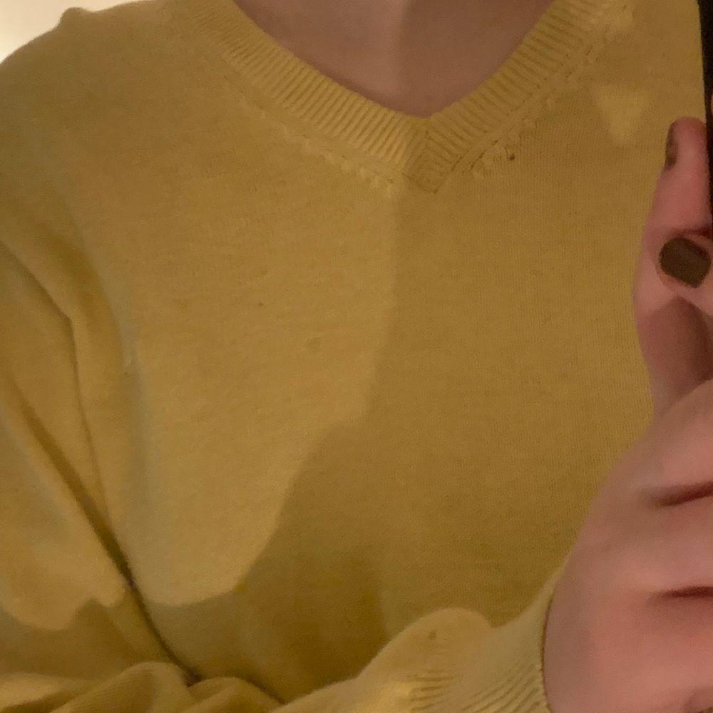 """V-ringad stickad """"grandpa sweater"""" i en mildare gul färg men inte pastell gul. Köpare står för frakt. Stickat."""
