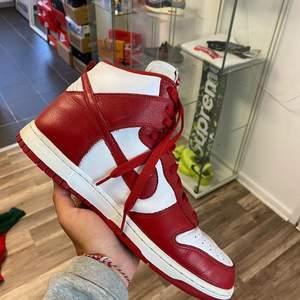 """Säljer mina fina Nike Dunk High Retro """"St Johns"""". Dom är pre owned men ändå i fint skick. Mycket sko för pengarna om man jämför med andra modeller. Historiskt rik design och colorway. Jag köpte dom från 2am club's instasida i juli 2020.     (Årsmodell 2016) (Storlek 10(44)) (Con 7/10) (Bud: 2690 bin: 2990) (ps har tagigt bort smutsen på gummit längst fram av vänstra foten)"""