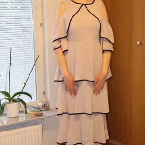 OBS! Bilderna beskärs på Plick så skriv privat för hela bilder! 😃 Beigerosa klänning med volanger och svarta detaljer. Aldrig använd och prislapp sitter kvar. Strl M/L. Möts upp eller fraktar, skriv privat för fraktkostnaden.