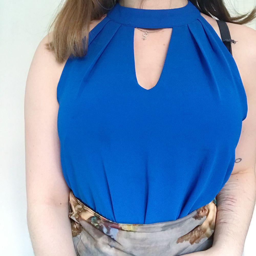 Ärmlös blus i cool blå färg från Rose + Olive köpt i USA. Sitter så fint på och har en snygg designad keyhole typ av neckline. Storlek S. Blusar.