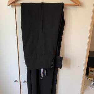 Svarta kostymbyxor med hög midja, knappar och vida ben🎩 benen har ca 1 dm slits.