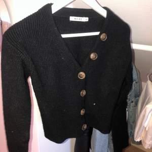 En svart stickad tröja med knappar från NAKD. Slutsåld på hemsidan, superfin och bra kvalitet! Bjuder på frakten!🤍