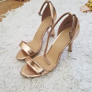 Snygga Rosé guldiga Sandaletter från märket New look, köpta på zalando. Slutsålda. Endast använda en gång inomhus. Tror att klacken är 6-7 cm hög. Sista bilden är lånad :-) inköpspris var 279kr. står ej för frakten