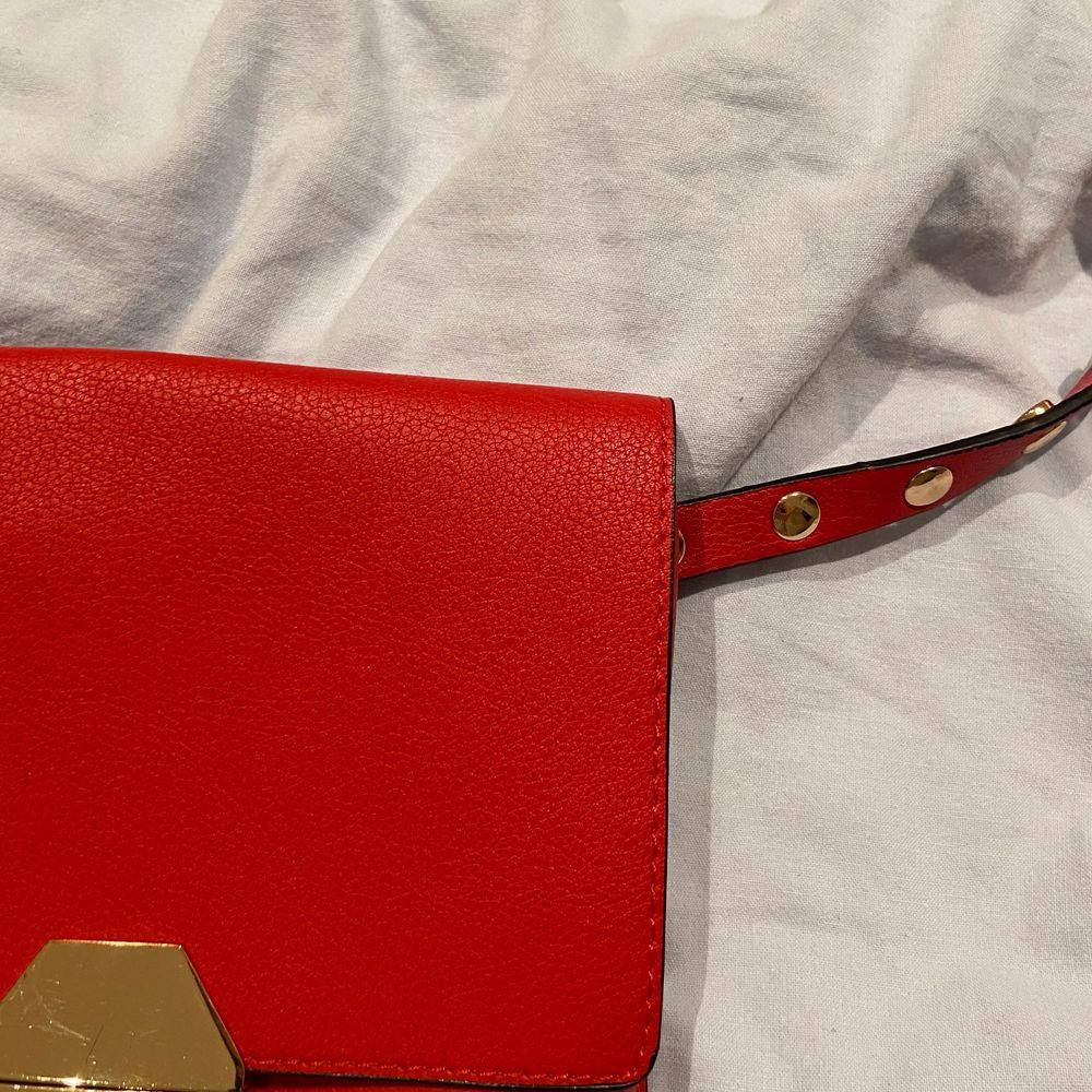 En röd väska med guldiga detaljer som funkar som både magkänsla och axelväska. Väskan är från Zara och priset är 70kr ❤️:). Accessoarer.