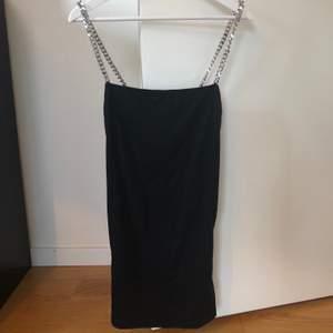 Svart klänning med kedjor och slits, endast använd en gång så fint skick. Köpt på Nelly, från märket motel.