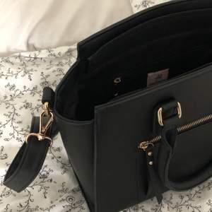 """Svart handväska med guldiga detaljer och avtagbart axelband från märket """"Anna Field"""". Använd som skolväska en termin och funkade perfekt för att få plats med böcker och dator, säljer på grund av att det inte är min stil längre, frakt tillkommer🤍 pris kan absolut diskuteras"""