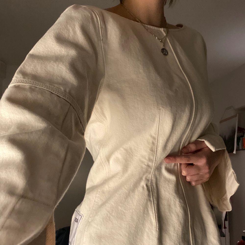 Unik kavaj i vit jeans! Man kan ha den som: 1. Vanlig kavaj/jacka. 2. Långärmad topp med utsvängda armar, tajtare i midjan. 3. Som kavaj med en insydd tubtopp. Kom aldrig till användning, så nyskick! Kan mötas upp i innersta Stockholm, annars får köparen stå för frakten🧚♀️. Kostymer.