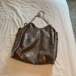 En oäkta stella mccartney väska köpt på minto i en fin brun glänsande färg! Den är ca 35 ca på bredden, och ca 30 på längden. Har inget långt band i mitten.