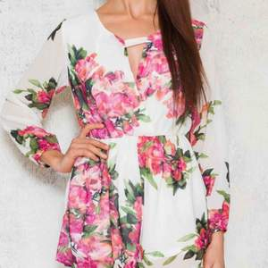 """Vit jumpsuit som faktiskt ser ut som en klänning. Från märket dmretro / dennis maglic. """"Ava Playsuit"""". Nypris är 599kr. Byxdress med blommönster använd EN GÅNG PERFEKT SKICK. Passar nog även S"""
