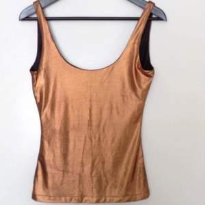 Festtopp i brons med djup rygg och tight passform.