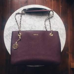 Äkta DKNY Purple Saffiano Burgundy Medium Tote Bag. Jättesvår färg att fånga på bild men den är mörklila, på sista bilden ser den nästan svart ut pga ljuset, men ville bara visa att den är i bra skick! Använd fåtal gånger, inga revor eller märken på väskan! Flera fack inuti och DKNY mönstrat foder. Gulddetaljer på kedjan och hänget vilket knappt syns men skickar jättegärna fler bilder vid förfrågan! Säljer pga inte riktigt min stil längre, nypris €236 men är villig att diskutera pris! Köpare står för eventuell frakt