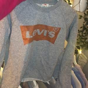 Grå sweater från levis med guldigt tryck. Såå fin men kommer inte till använding längre. OBS! Lite croppad men går absolut över magen. Frakt tillkommer