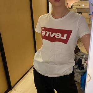 """Vit fin mjuk Levis t-shirt med stort rött Levis märke fram.❤️🤍 Mycket bra skick, då den endast är använd ett fåtal gånger och tvättad kanske en eller två gånger. Material 100% bomull. (Säljer pga för liten och inte riktigt min stil längre). Jättefin, jättemjuk, bekväm och snygg till tex jeans. Storlek XS så på mig som är XS/S är den lite liten, men om man vill att den ska vara taight så är den ganska lagom. (Se hur den sitter på mig på första bilden). DM vid intresse/frågor/fler bilder.❣️(Det kan du göra här under där det står """"kontakta""""). Avhämtning på Södermalm eller frakt till självbetalningspris.:)"""