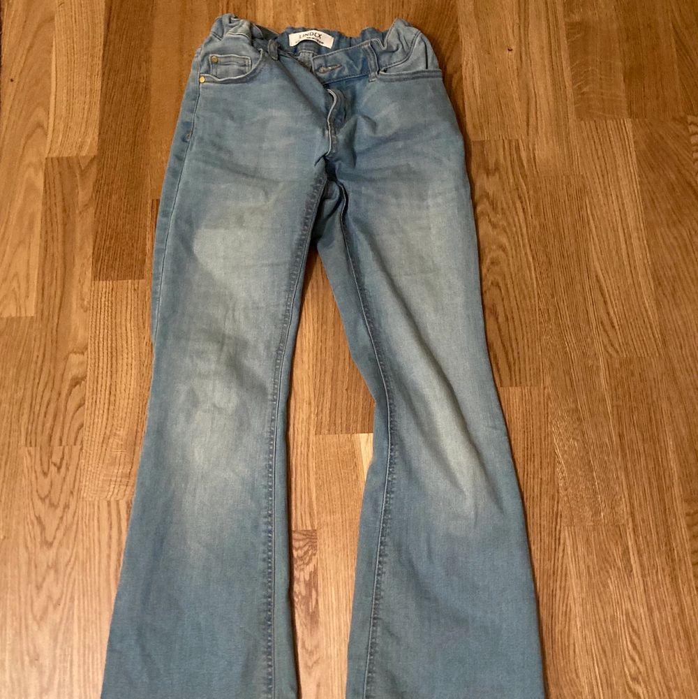 Ett par lågmidjade bootcut jeans från Lindex är i barnstorlek men sitter som XS/XXS. Man kan spänna den i midjan eller gör den större. Den är väldigt kort så om du är lång kommer den inte passa dig. Är i bra skick. Pris kan diskuteras.. Jeans & Byxor.