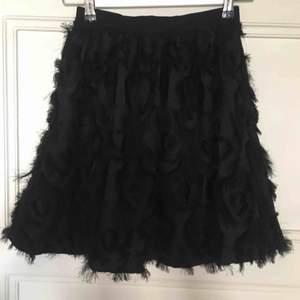Svart, helt oanvänd kjol med fjädrar. Säljer pga inte min stil. Storlek 34, köpt för 249kr säljer nu för 100kr! Frakt tillkommer!