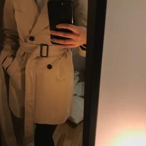 Säljer en oanvänd beigh kappa från Vero moda, storlek 34 grymt fin inför våren, köpt för 500kr säljs för 190kr