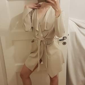 Classy beige cardigan trench coat i skönt stretchigt material, med skärp som går att knyta i midjan. Märke: Mirelle. Har några mörka fläckar baktill, bilder kan skickas på dessa på förfrågan. Frakt tillkommer med 48 kr.