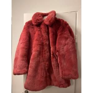 Helt oanvänd röd pälsjacka från H&M. Prislappen sitter kvar.