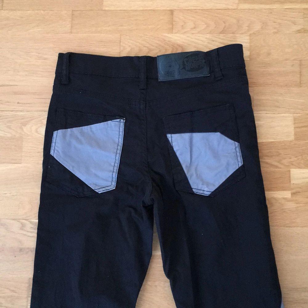 Ett par svarta och grå byxor i lite ovanligt
