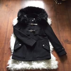 Snygg, populär kappa från Zara med gulddetaljer och stor huva i fuskpäls.   Kappan har använts sparsamt under en höst. Nypris 1800kr.