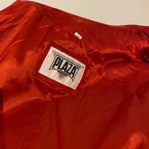 Ett rött set med kjol och jacka/kavaj i rött skinn! Kjolen har dragkedja och tryck-knapp baktill och även slits. Jackan är lite fälld på ärmarna som syns på bild 3, men själva setet i sig är knappt använt. Det är fodrat och passar perfekt till något ex ett basplagg!    Bra kvalite och extraknapp till jackan finns medsytt på insidan.