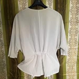 Öppen blus i off white, kimonoinspirerat snitt, mycket tunn matt viskos, half sleeve. Dunder över bodycon-klänning, alternativt som bardcore/cottagecore/fairycore-dröm med lång eller kort kjol.