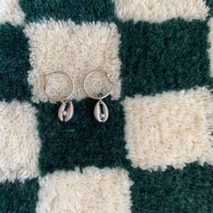 Silvriga örhängen med äkta pärla i mitten. Möts gärna upp i Stockholm alt står köparen för frakten