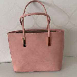 Rosa normal stor väska, flertal små fack inuti och ett utanpå. Bra kvalitet, inte så använd då färgen inte riktigt passar mig.