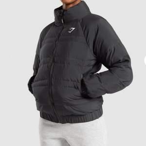 Jätteskön och fin Gymshark jacka. Nypris 650kr.Endast använd ett par gånger. Strl S. 🖤  - Puffer jacket - Full-length zip to front with branded puller - Zipped pockets to each side - High neck collar - White printed logo to chest - Exterior: 100% Polyester. Lining: 100% Polyester.