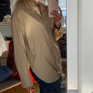 Beige skjorta från Gina Tricot i storlek 38. Använd ett fåtal gånger så i bra skick. Modellen är stor och luftig, skulle säga att den passar de flesta beroende på önskad passform. Jag på bild är 172 cm och har vanligtvis storlek M.