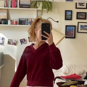 Mörkröd plysch-aktig V-ringad tröja. Köpt second hand men har själv aldrig använt den. Lite stretchigt material så passar nog nån storlek större oxå.