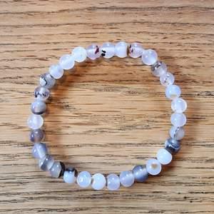 Armband med 6 mm stora kristallpärlor av agat.  Rundslipade stenar trädda på elastisk tråd. Ca 16 cm omkrets. Skickas i vadderat kuvert via postnord.
