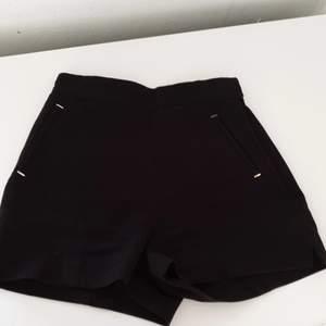 Svarta kostym-shorts med liten slits på sidan av benen, snygga fickor framtill, fake-fickor på rumpan, dragkedja på vänster sida med små krokar o en knapp i midjan. De är högmidjade o sitter snyggt, använda men hela o fina! Hör av er vid funderingar eller för fler bilder✨