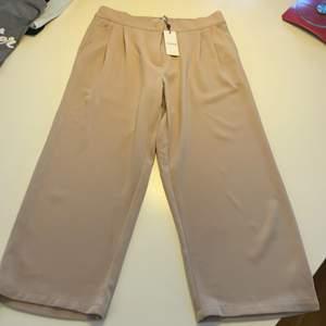 Lite kortare byxor i löst material, beiga. Oanvända med lappen kvar från pieces/veromoda