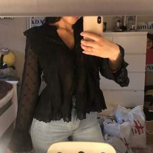 En svart blus, köpt från H&M. Har jätte fina detaljer med volanger osv. Använd enstaka gånger men helt felfri.