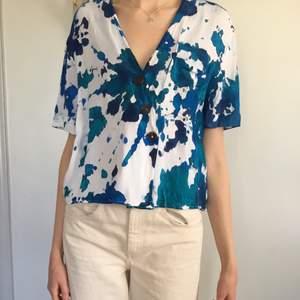 Magisk havsinspirerad batik skjorta i färgerna turkos, blå och marinblå. Knapparna på skjortan går i brunt. Strl M. 🌊